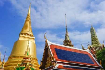 Ancient city museum of Thailand style architecture, including golden pagoda and red blue traditional roof tile and spire on the top. Also has beautiful pattern detail at the gable. uprisen angle view. 版權商用圖片