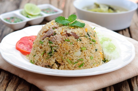 fried rice: Fried rice with chili sauce and soup on wooden table