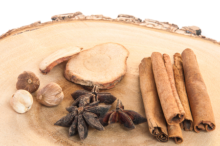 recipe background: Dry spices on wooden chopping block