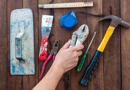 herramientas de construccion: Herramientas de mano de construcci�n con la mano sobre el piso de madera