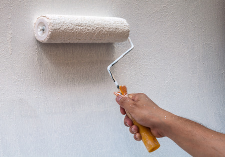 wall paint: Hand holding rolling paint brush, wall painting