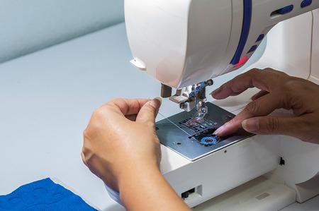 maquinas de coser: La mujer se est� poniendo hilo en su m�quina de coser