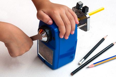 Un niño está afilando el lápiz mecánico usando afilador sobre fondo blanco