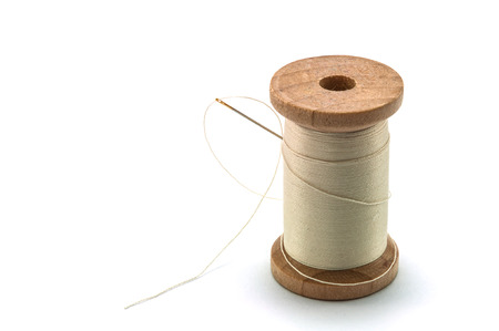 spool: Isolated wooden spool of cream thread with a needle Stock Photo