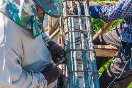 reinforcing bar: Construction workers are installing steel rods in reinforced concrete beam Stock Photo