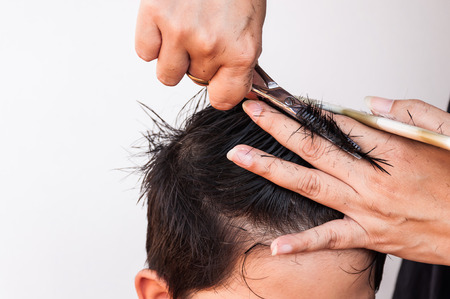 dresser: Hair dresser is cutting a boy hair over white background, focus at scissor
