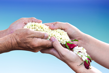 over paying: Young hands give jasmine garland to the older over light blue gradient background. Thai tradition for any special family occasions for paying high respective with love and care. Stock Photo