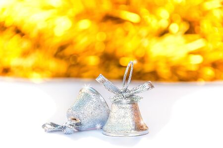 silver bells: Silver bells with blur shiny yellow stripe and white background, Christmas decoration object Stock Photo