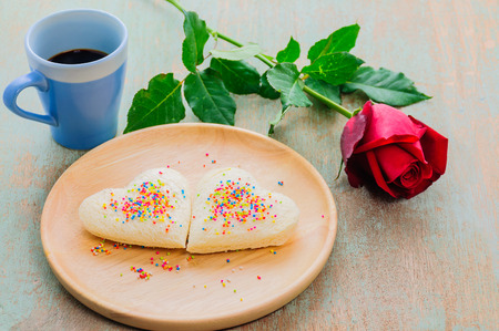 rose photo: Couple of heart shape white bread on wooden plate with coffee cup and red rose. Photo is focused at the bread. Stock Photo