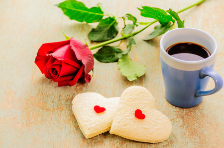 rose photo: Couple of heart shape white bread with coffee cup and red rose. Photo is focused at the bread.