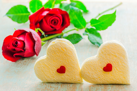 rose photo: Couple of heart shape white bread and red rose. Photo is focused at the bread. Stock Photo