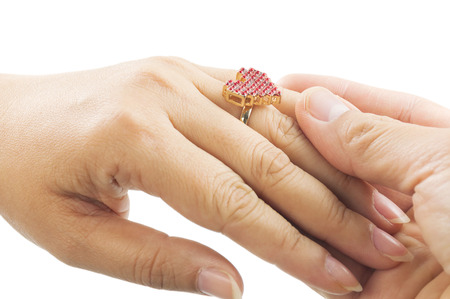 ring finger: Close up of mans hand is putting heart shape ring to womans ring finger over white background Stock Photo