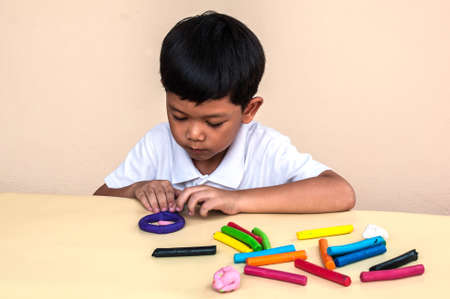 art and craft: A boy is playing colorful clay
