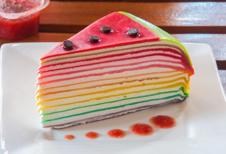 Rainbow crepe cake on a wooden table 免版税图像