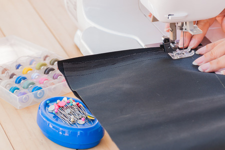 sewn: Womans hand made patchwork of using her sewing machine needles are sewn up quickly