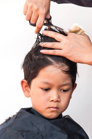 dresser: A boy is cut his hair by hair dresser over white background, focus at his right eyes