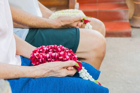 Old female hand holding rose garland and blurred old male hand holding jasmine garland. Thai tradition for any special family occasions when younger pay high respective to there older family members.