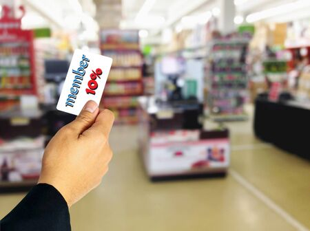 superstore: Businessman holding member card discount ten percent overlay on blurred superstore.