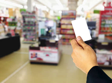 superstore: Businessman holding empty white card overlay on blurred superstore.