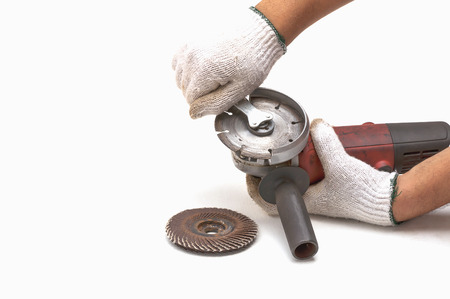 Worker is removing blade of angle grinder, hand tool, focus at blade and isolated over white.