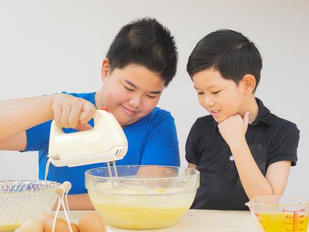 cake mixer: Kids are making cake using hand mixer machine