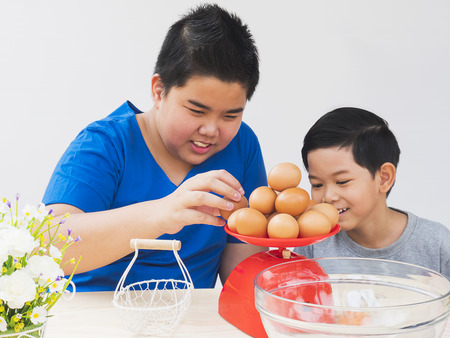 weigh machine: Children are happily weighing raw eggs preparing to make a cake. Photo is focus at the eggs. Stock Photo
