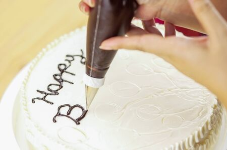 Cake decorating using piping tip for writing a word Stock Photo