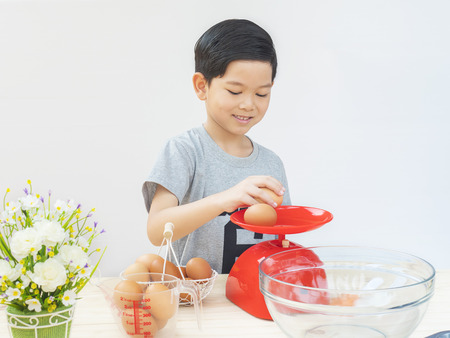 weigh machine: A boy is weighing raw eggs preparing to make a cake.