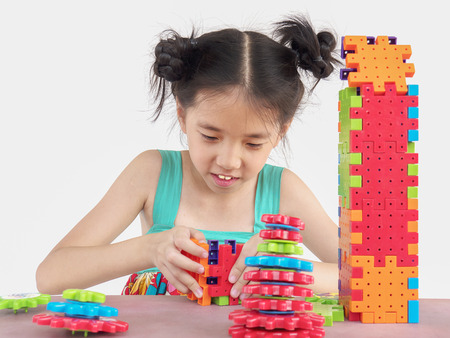 consciously: Asian child is playing puzzle plastic block creative game to practice their physical and mental skill