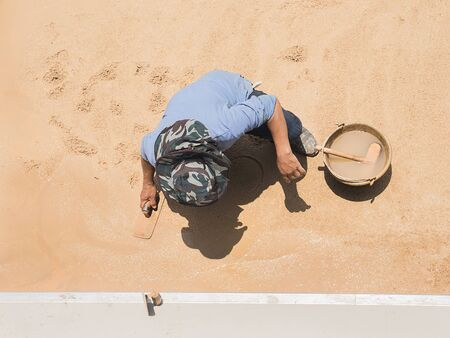 light worker: A construction worker is making sand wash floor, outdoor work under day time strong sun light and shadow