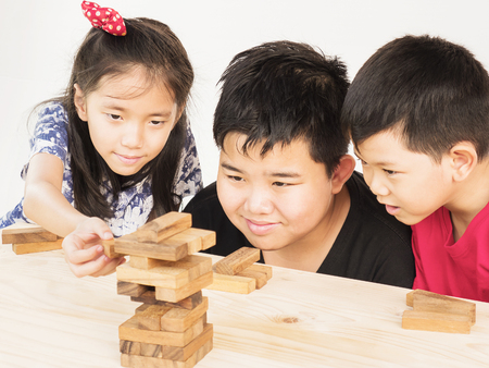 Children is playing a wood blocks tower game for practicing their physical and mental skill