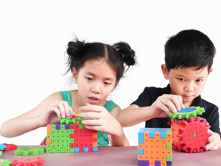 Aziatische kinderen spelen puzzel plastic blok creatief spel om hun fysieke en mentale vaardigheid te oefenen