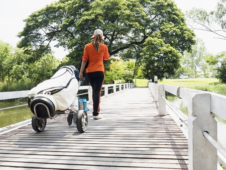 caddie: Golf caddy is walking with her trolley Stock Photo