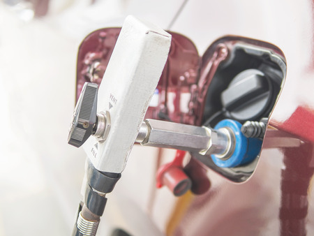 ngv: NGV, Natural Gas Vehicle, head dispenser with a car at the gasoline station in Thailand Stock Photo