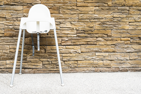 baby chair: Baby chair with sand stone wall background Stock Photo