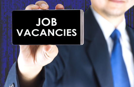job vacancies: Job vacancies word on mobile phone screen in blurred young businessman hand and digital technology background