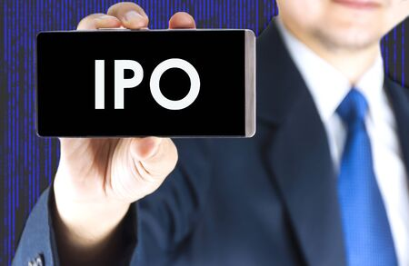 initial public offerings: IPO, Initial Public Offering, word on mobile phone screen in blurred young businessman hand and digital technology background, business concept