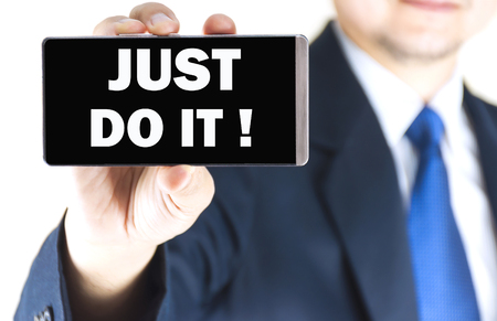 JUST DO IT word on mobile phone screen in blurred young businessman hand over white background, business concept