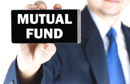 mutual fund: MUTUAL FUND word on mobile phone screen in blurred young businessman hand over white background, business concept Stock Photo