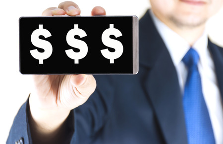 tripple: White tripple dollar sign, $$$, character on mobile phone screen in blurred young businessman hand over white background, business concept
