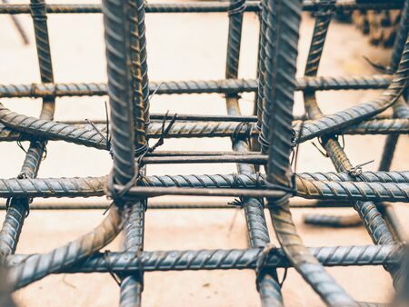 site preparation: Vintage style photo of selective focused steel rods in reinforced concrete footing and column preparation in construction site.