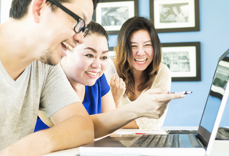 Two women and one man are happily looking at computer in modern office