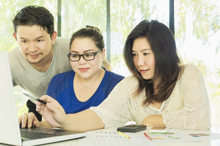 two women and one man: Two women and one man are working with at computer in modern office Stock Photo