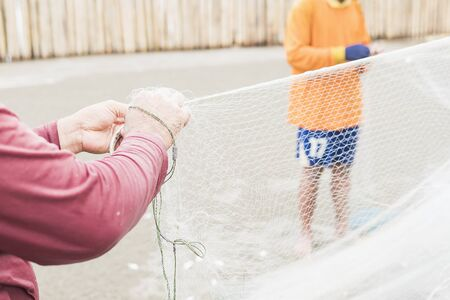 Fisherman are releasing fish from their trawl on a beach