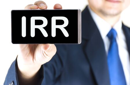 rate of return: IRR, Internal Rate Of Return, word on mobile phone screen in blurred young businessman hand over white background, business concept