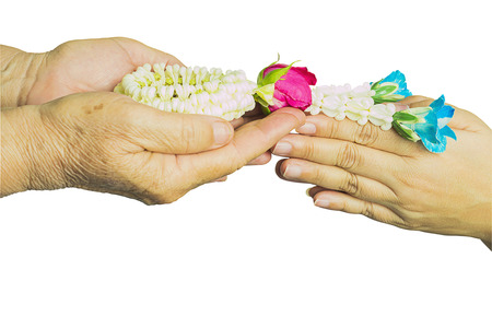 over paying: Young hands give jasmine garland to the older isolated over white. Thai tradition for any special family occasions for paying high respective with love and care. Photo includes CLIPPING PATH. Stock Photo