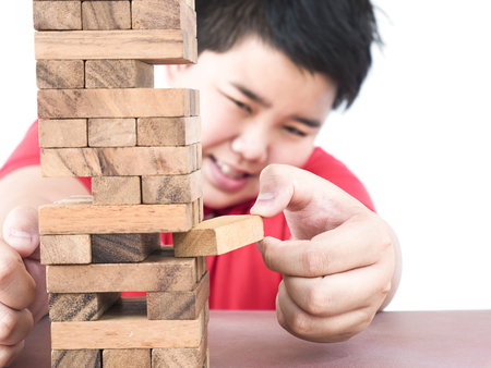 consciously: Asian kid is playing a wood blocks tower game for practicing physical and mental skill