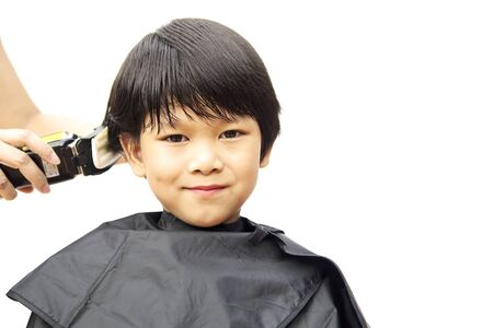 hair dresser: A boy is cut his hair by hair dresser isolated over white background