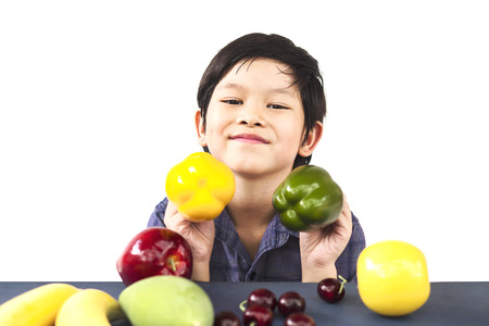 Asian healthy boy showing happy expression with variety colorful fruit and vegetable over white background