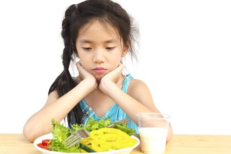 Asian lovely girl showing boring expression with fresh colorful vegetables and glass of milk isolated over white background Stock Photo